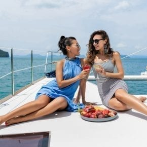 Girlfriends relaxing on the yacht. Two girls celebrating a birthday on the yacht. Beautiful girls drink champagne and eat tropical fruits.